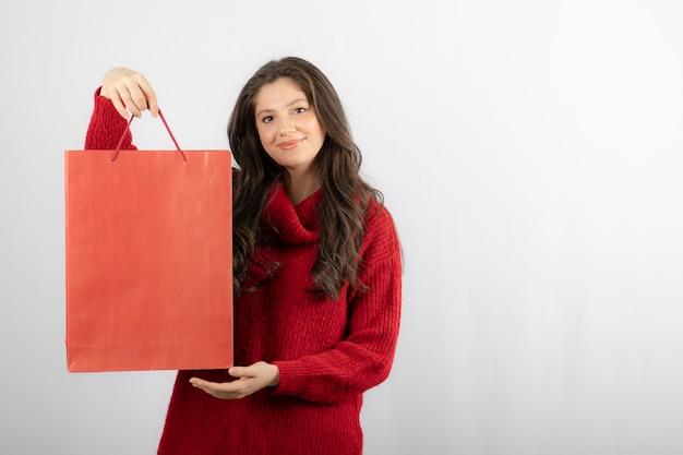 Foto di una signora felice che mostra le sue borse della spesa colorate.