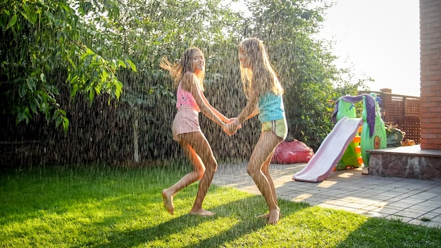Photo of happy laughing children in wet clothes jumping and dancing under warm rain at garden. family playing and having fun outdoors at summer