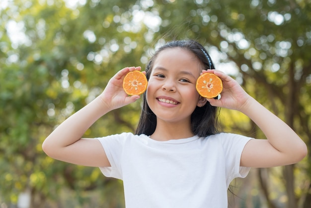 Photo happy little asian girl child standing showing front teeth with big smile. covering eyes with orange with abstract blurred foliage and bright summer.
