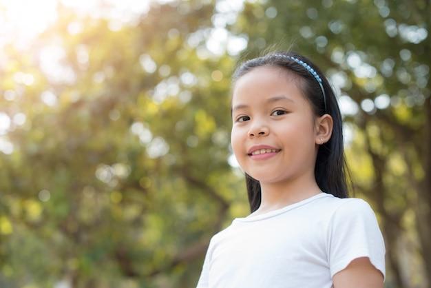 Фото счастливый маленький азиатский ребенок девочка стоя с большой улыбкой с абстрактной запачканной листвой и ярким солнечным светом лета. концепция счастливой семьи