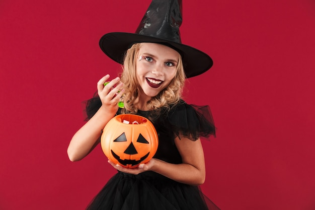 Photo of happy little girl witch in carnival halloween costume