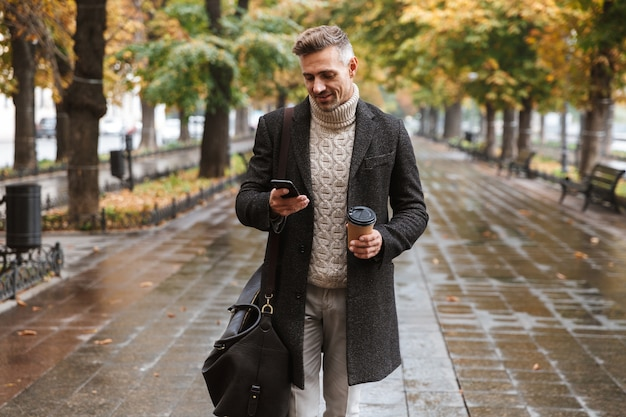 Photo of happy man 30s wearing warm clothes walking outdoor through autumn park, and using mobile phone