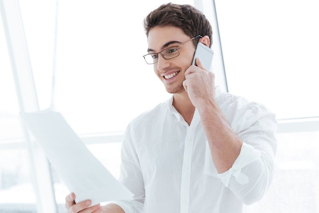 Photo of happy man dressed in white shirt talking by phone near big white window. look at documents.