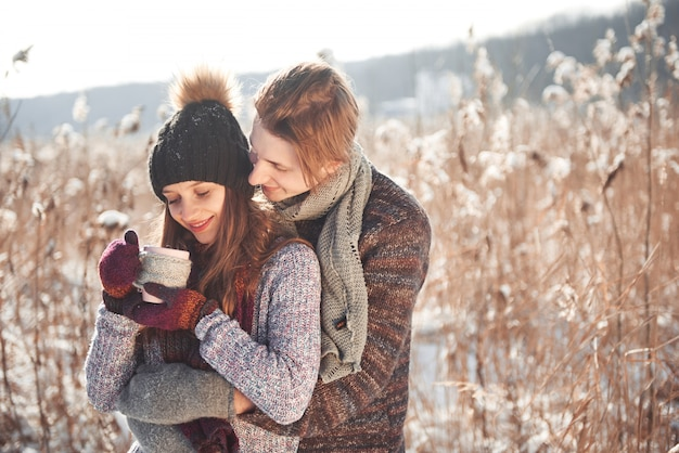 Photo of happy man and pretty woman with cups outdoor in winter. winter holiday and vacation. christmas couple of happy man and woman drink hot wine. couple in love