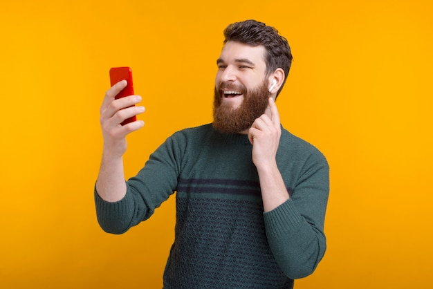 Photo of happy man talking on smartphone with wireless headphones over yellow background