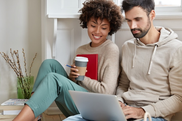 Photo of happy multiracial male and female friends watch video on laptop computer, have leisure time at home.