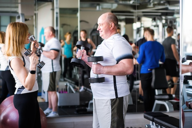 Photo of happy older married couple doing exercises with dumbbells.
