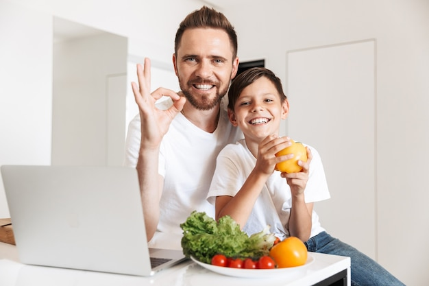 Photo of happy smiling father and son reading recipe on laptop, for cooking meal with vegetables in kitchen