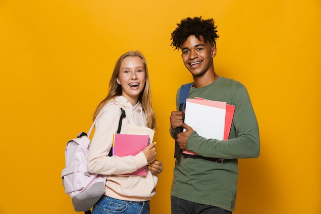 Photo of happy students guy and girl 16-18 wearing backpacks smiling and holding exercise books, isolated over yellow background