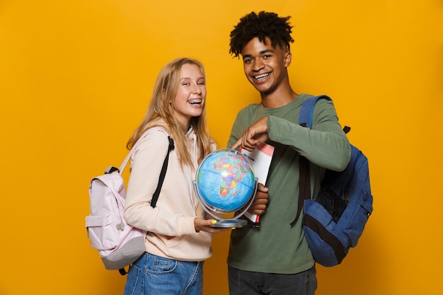 Photo of happy students man and woman 16-18 wearing backpacks holding earth globe and exercise books, isolated over yellow background
