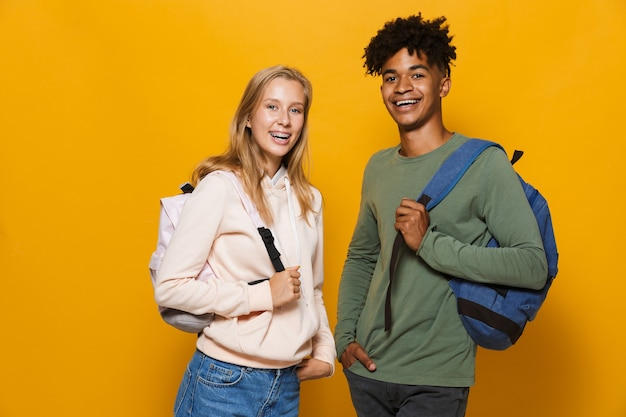 Photo of happy students man and woman 16-18 wearing backpacks laughing at camera, isolated over yellow background