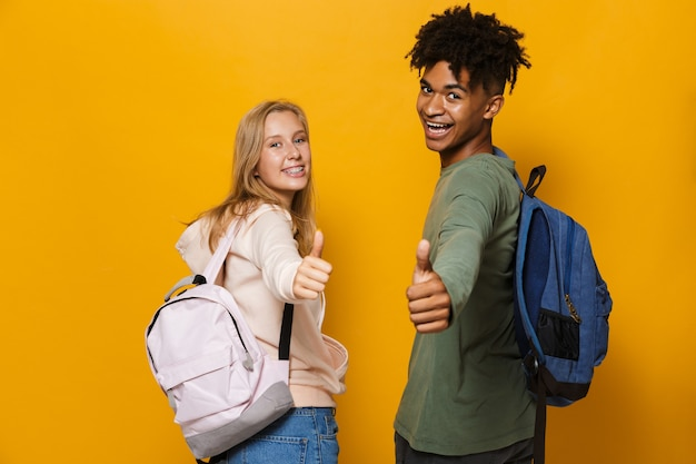 Photo of happy students man and woman 16-18 wearing backpacks laughing and showing thumbs up, isolated over yellow background