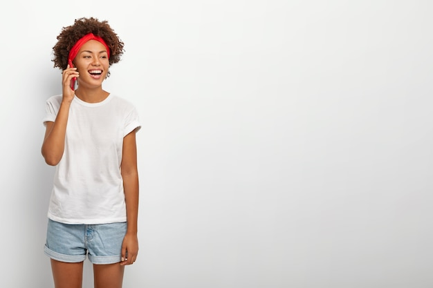 Photo of happy teenage girl with afro hairstyle, red headband, wears white casual t shirt and jean shorts, focused away, has funny telephone conversation with friend, isolated over white background