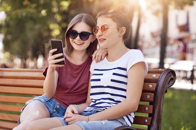 Photo of happy teenage girls message in social networks, use smart phone for entertainment, wears trendy sunglasses, pose on wooden bench outdoor, connected to wireless internet. leisure concept