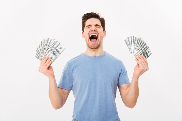 Photo of happy winner man in casual t-shirt holding two fans of money dollar banknotes, isolated over white wall