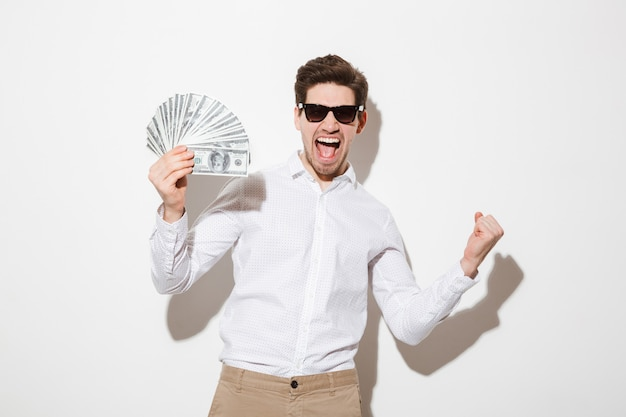 Photo of happy winner man in shirt and sunglasses screaming and holding fan of money in dollar banknotes with clenched fist, isolated over white wall with shadow