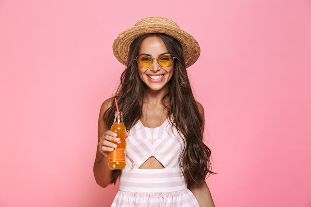 Photo of happy woman 20s wearing sunglasses and straw hat drinking juice from glass bottle, isolated over pink wall
