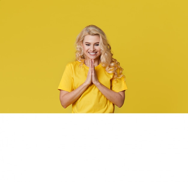 Photo of a happy young blond woman standing isolated over yellow wall