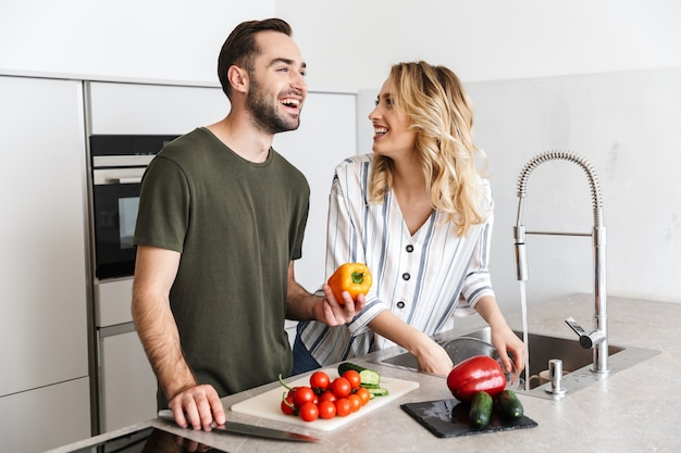 Photo of a happy young loving couple indoors at the kitchen cooking vegetable salad have a breakfast.