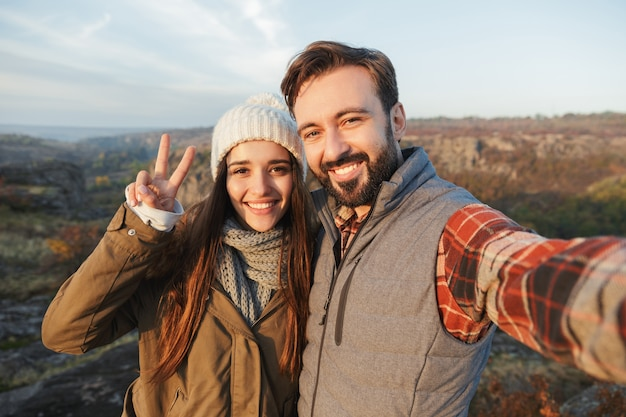 Photo of happy young loving couple outside in free alternative vacation camping over mountains take selfie by camera showing peace gesture.