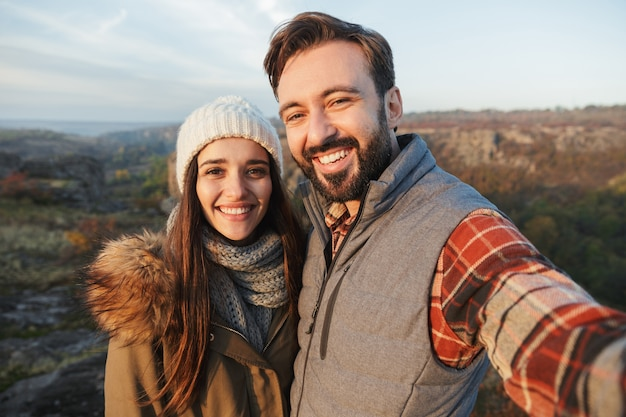 Photo of happy young loving couple outside in free alternative vacation camping over mountains take selfie by camera.