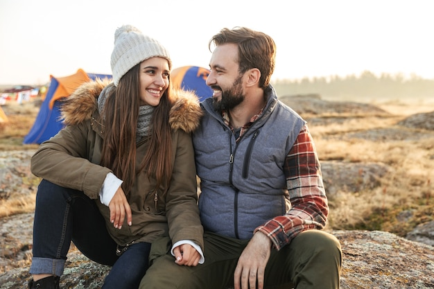 Photo of happy young loving couple outside with tent in free alternative vacation camping over mountains.
