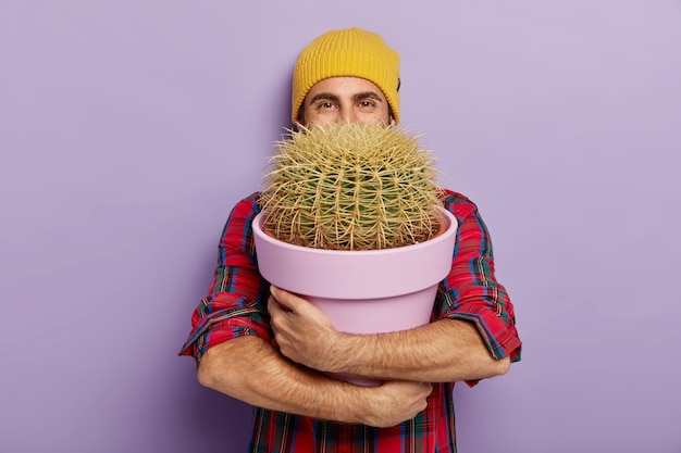 Photo of happy young male flower grower embraces big pot with prickly cactus, wears stylish hat and checkered shirt, glad to receive house plant as gift, isolated on purple wall. gardening concept
