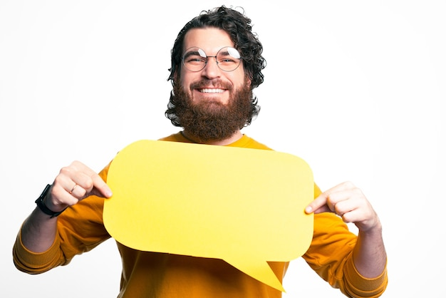 Photo of happy young man with beard holding empty speech bubble