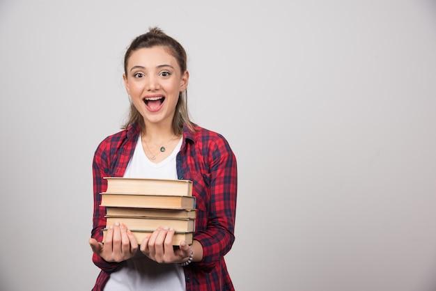 Foto di un giovane studente felice in possesso di una pila di libri.