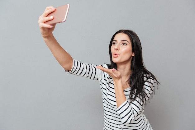 Photo of happy young woman send kissed while make a selfie over grey surface. look at phone.