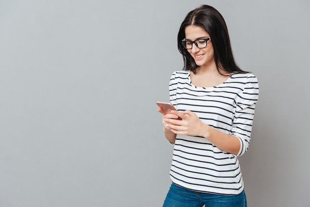 Photo of happy young woman wearing eyeglasses chatting by phone over grey surface. look at phone.