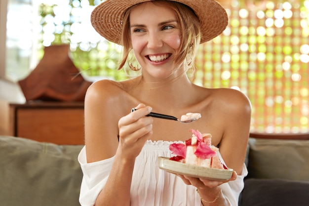 Photo of happy young woman with broad smile, eats tasty dessert at cafeteria, enjoys summer party with friend, listens interesting funny story from interlocutor. people, rest and eating concept