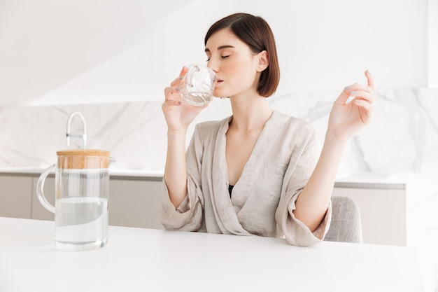 Photo of healthy brunette woman waking up in morning and drinking still fresh water from transparent glass, in white flat