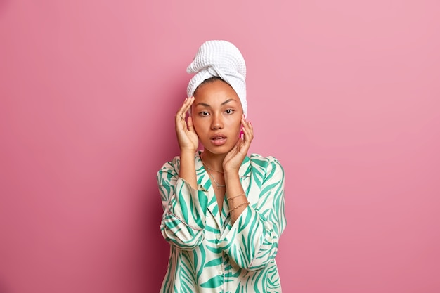 Photo of healthy serious ethnic woman has smooth fresh skin after taking shower touches face gently wears casual nightwear wrapped bath towel on head. natural beauty