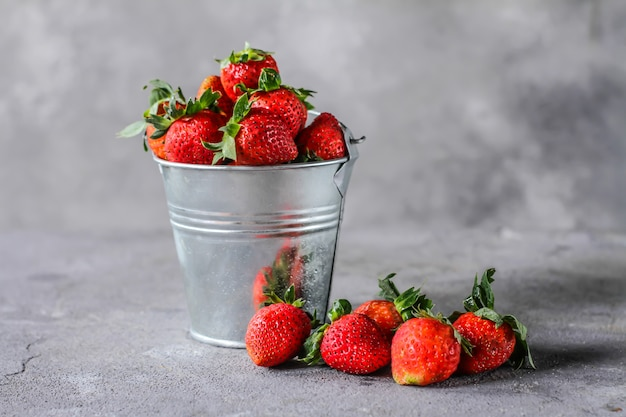 Photo of heap of fresh strawberries in the bowl on rustic grey background. a bunch of ripe strawberries in a can bowl on the table. copy space. healthy fresh fruit. organic food. clear food
