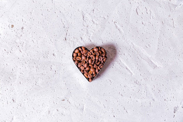 Photo of heart-shaped coffee beans copy space on concrete background. horizontal photo. top view