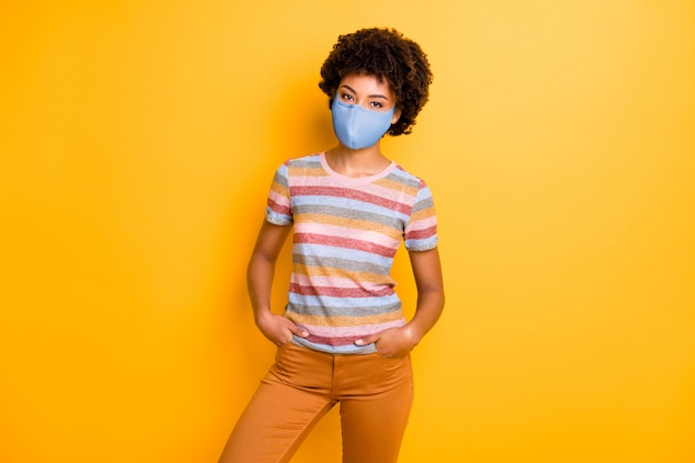 Photo of her she healthy attractive wavy-haired girl wearing safety textile reusable mask viral pneumonia wuhan contamination prevention isolated bright vivid shine vibrant yellow color background