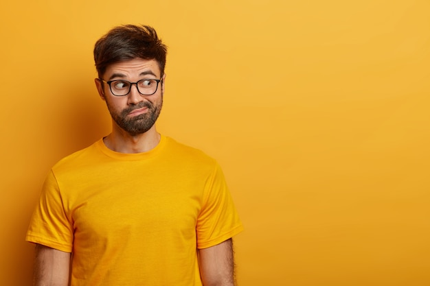 Photo of hesitant bearded man looks aside, smirks face and has puzzled expression, tries to decide something, dressed in casual yellow t shirt, poses over vibrant  wall, wonders what he sees