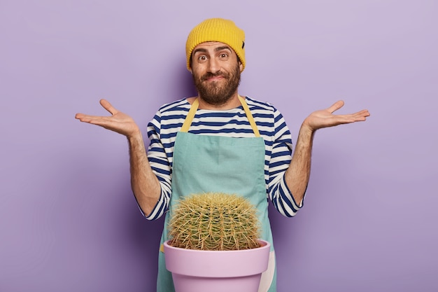 Photo of hesitant male florist spreads palms sideways, has unaware face expression, wears special uniform, isolated over purple background. botany concept