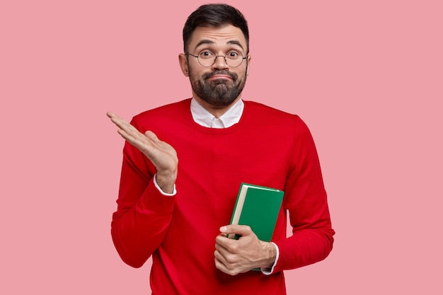 Photo of hesitant young unshaven male business owner has clueless unaware expression, raises palm in bewilderment, holds notebook