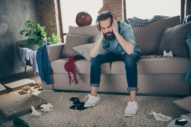 Photo of hipster crazy guy sitting sofa holding head intoxicated food underwear lying floor had stag party suffer hangover morning headache messy flat indoors