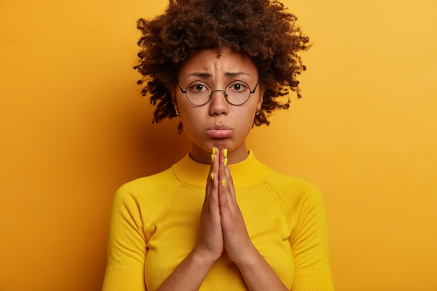 Photo of hopeful displeased afro american woman makes cute eyes, sobbing expression, says please, wants something badly, presses palms together, asks for favor, pleads apology, wears round spectacles