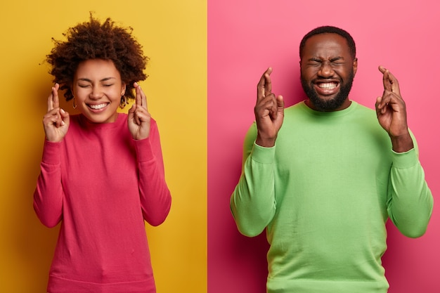 Photo of hopeful lucky afro america woman and man cross fingers for good luck, believe fortune will come, hope wish fullfill, anticipate miracle happened, pose against yellow and pink wall