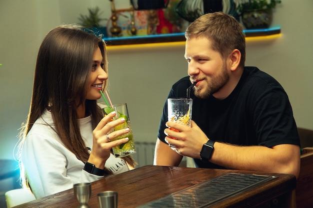 술집에서 유혹하는 섹시한 젊은 부부의 사진 가로 및 칵테일 음료