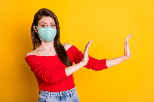 Photo of horrified terrified girl in medical mask hold hand block way covid infection spread wear red style stylish trendy top denim jeans isolated bright shine color background