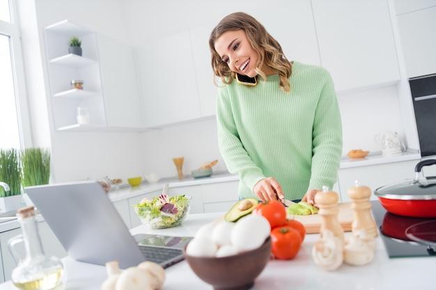 Photo of housewife knife cut avocado cook look online recipe notebook talk phone
