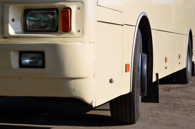 Photo of the hull of a large and long yellow bus. close-up front view of a passenger vehicle for transportation and tourism