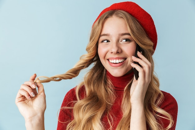 Photo of humble girl 20s wearing red beret talking on cell phone isolated