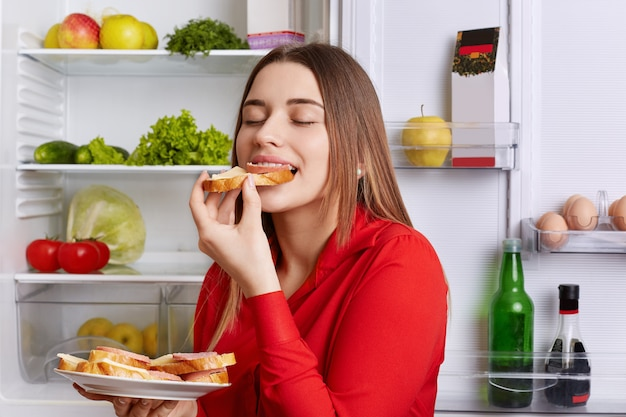 Photo of hungry young cute woman eats with appetite tasty sausage sandwhich, comes after work, stands near opened refrigerator, closes eyes with pleasure. people, eating and nutrition concept
