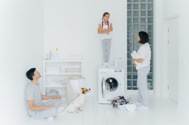 Photo of husband and wife, their dog and daughter do housework in laundry room